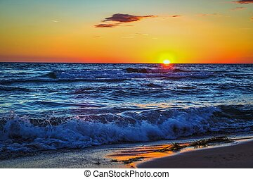 Dramatic sunset over the blue waves of the Lake Michigan horizon.