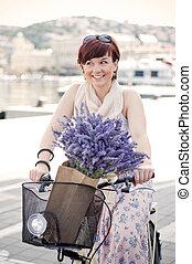 Summertime biking - Women riding a retro bike with lavender...