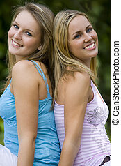 Summertime Friends - Two beautiful young women sitting back...