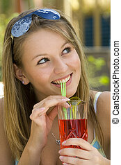 Summertime Fun - A young lady drinking a tall drink outside...