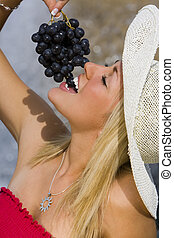 Summertime Grapes - A beautiful young blond woman sitting in...