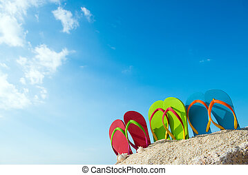 Summertime - Row of colorful flip flops on beach against...