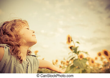 Summertime - Happy child in sunflower field. Freedom concept