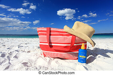 Summer sun protection at the beach, each hat and sunscreen on the sand at he beach. Logos removed