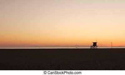 Summertime travel concept. Dark silhouette, iconic retro wooden lifeguard watch tower against sunset orange sky. Contrast watchtower outline, california pacific ocean beach twilight aesthetic, USA.