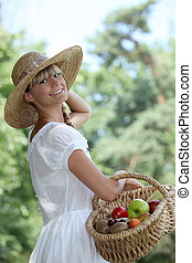 Summery woman in a straw hat holding a basket of fruit
