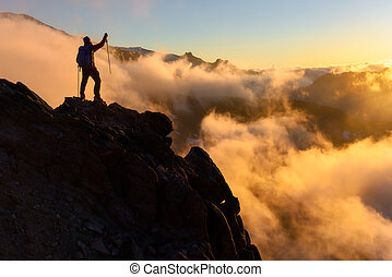 Inspiration theme of man standing on top of a cliff with rolling clould. Mount Rainier National Park, Washington, at sunset