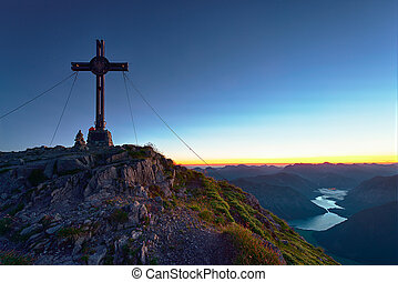 summit cross on mountain with lake in valley at sunrise