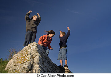 Summit - Three children cheering on a big rock against a...
