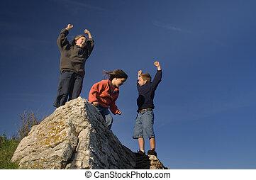 Summit - Three children cheering on a big rock against a...