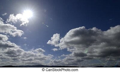 Fast flowing clouds with sun in the blue sky