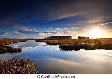 sun star at sunrise over blue lake in Drenthe