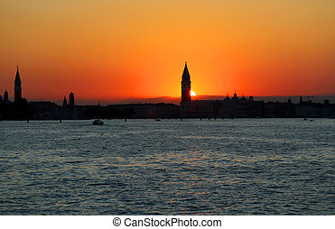 Sun at SUNSET in VENICE in Italy and the Campanile of St. Mark