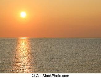 sun at sunset on the ocean
