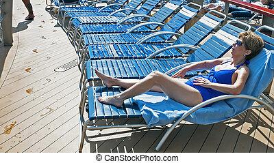 Sun Bathing - Woman sun bathing near a cruise ship pool on...