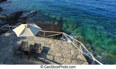 Sun-beds and umbrella near clear water, Crete