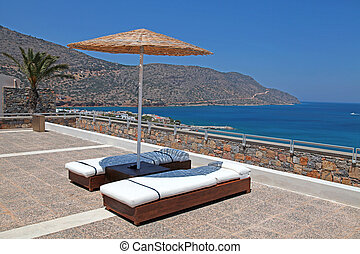 Sun beds and umbrellas on terrace in a luxury summer resort with Mediterranean sea view (Crete, Greece).