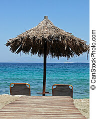 sun beds on a beach under a grass parasol looking out to see