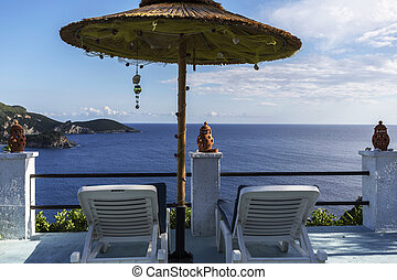 Sun beds under an umbrella in Greece