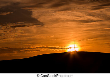 Cross on a hill with a bright sun setting behind it.