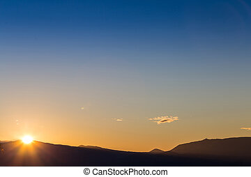 Sun behind dark mountain silhouettes, with blue and orange colored sky