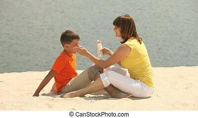 Sun-block - Mother putting sun blocking cream on her...