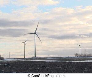 sun illuminated clouds in sky and windmills. alternative renewable wind energy.