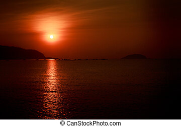 sun disk among red sky fishing boats on horizon at sunrise
