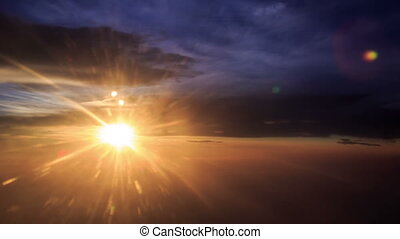 Sun Disk on Skyline above Clouds out of Airliner at Sunset -...