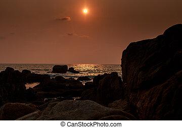 sun disk over sea dark rocks of fantastic shape on foreground