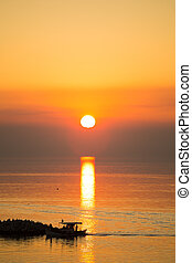 Sun disk reflecting on sea surface, with orange color dominating the seascape