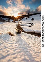 sun down over mountain river in winter