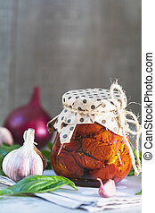 Sun dried tomatoes in glass jar on wooden background - Sun...