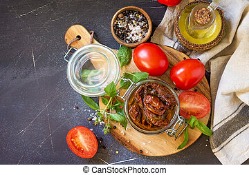 Sun dried tomatoes with olive oil in a jar on black stone or concrete table. Top view flat lay background. Copy space.