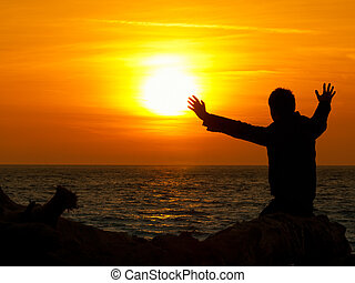 Sun gazing - man sitting by the sea with his arms raised to ...