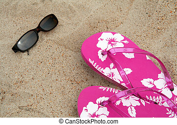 Sun glasses and pink flip-flops in the sand at the beach