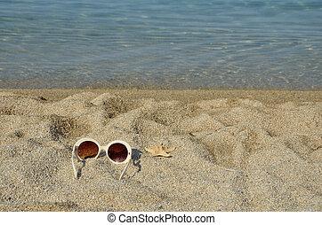 Sun glasses with sea star on a beach