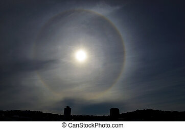 Sun with circular rainbow - sun halo occurring due to ice crystals in atmosphere above Wellington city skyline, New Zealand.