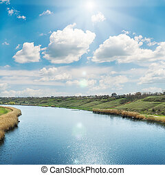 sun in blue sky over clouds and river with reflections