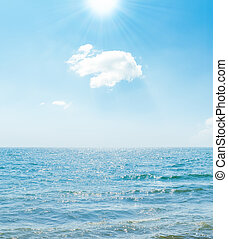 sun in blue sky over sea