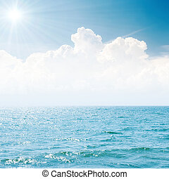 sun in blue sky over white clouds and sea