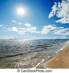 sun in blue sky with clouds over sea