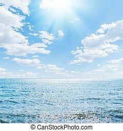 sun in clouds over blue sea