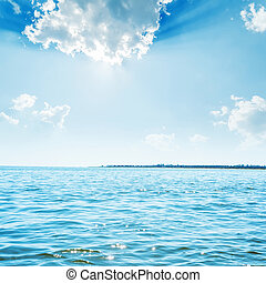 sun in clouds over blue sea with reflections