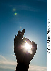 Sun in the hand on blue sky