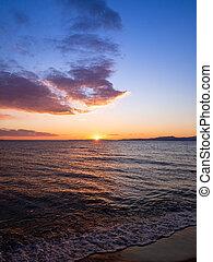 Sun is setting on the beach in Kavala, Greece