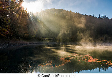 sun light in fog over the mountain lake Synevyr. high...