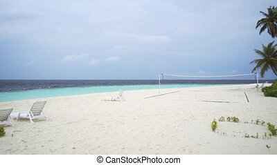 Sun Loungers and Volleyball Net on a Beach in the Maldives -...