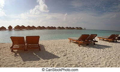 Sun Loungers offer View of Bungalows at Tropical Beach...