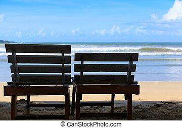Sun loungers on beach face the sea